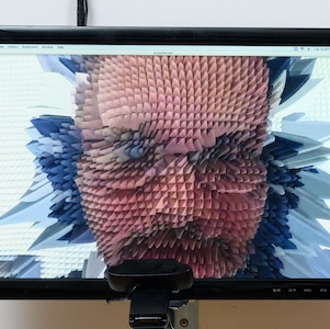 Monitor with a digital constructed image of the artist, a webcamera points at the screen.