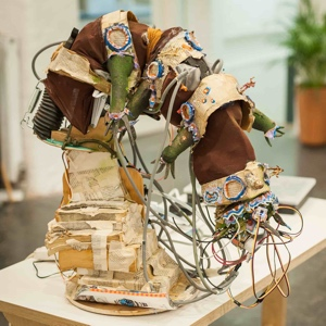 A soft robot sits on a table, looking like a tardigrade, made out of recycled materials, wires and sensors.
